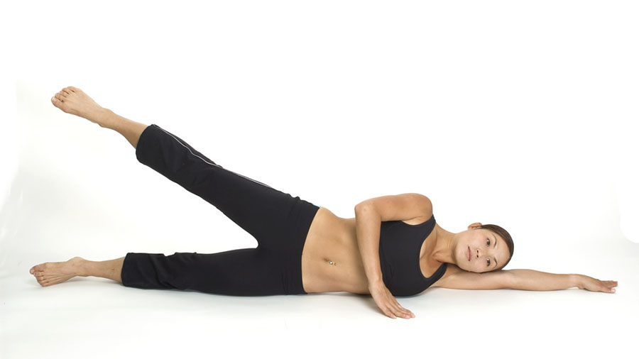 A female fitness instructor demonstrates the finishing position of the lying side leg raise