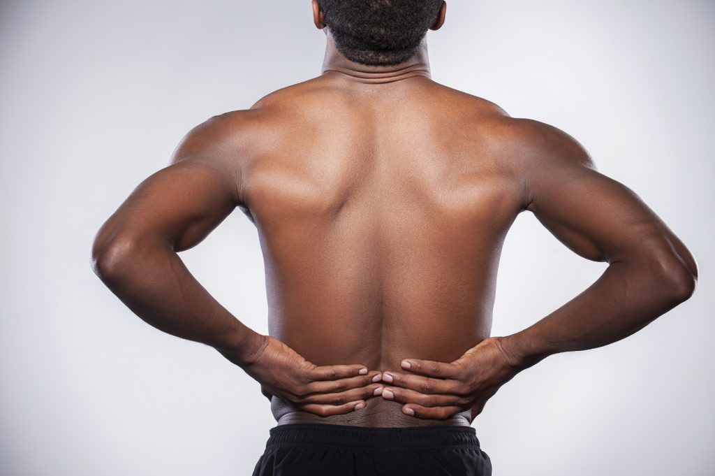 Backache. Rear view of young muscular African man touching his hip while standing against grey background