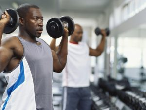 Two mid adult men exercising in a gym with dumbbells